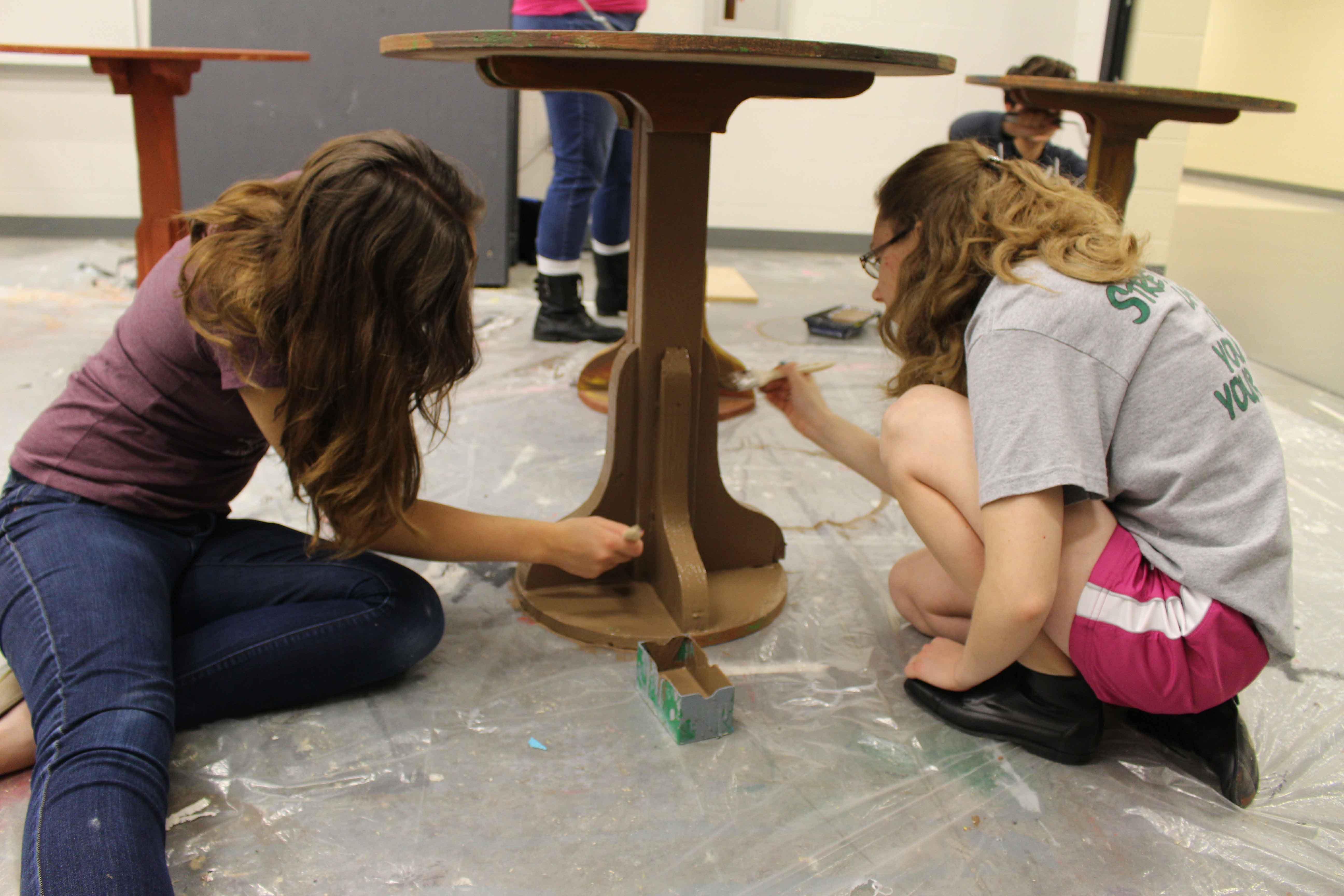 """•Working to get all of the props finished in time, seniors Anna Ohmart and Courtney Hittle paint one of the tables for a café scene on Oct. 28. Anna has been in Stagecraft for 2 years. """"I was in Stagecraft last year. I really enjoyed building sets and stuff,"""" said Ohmart. """"I really like working with my hands."""""""
