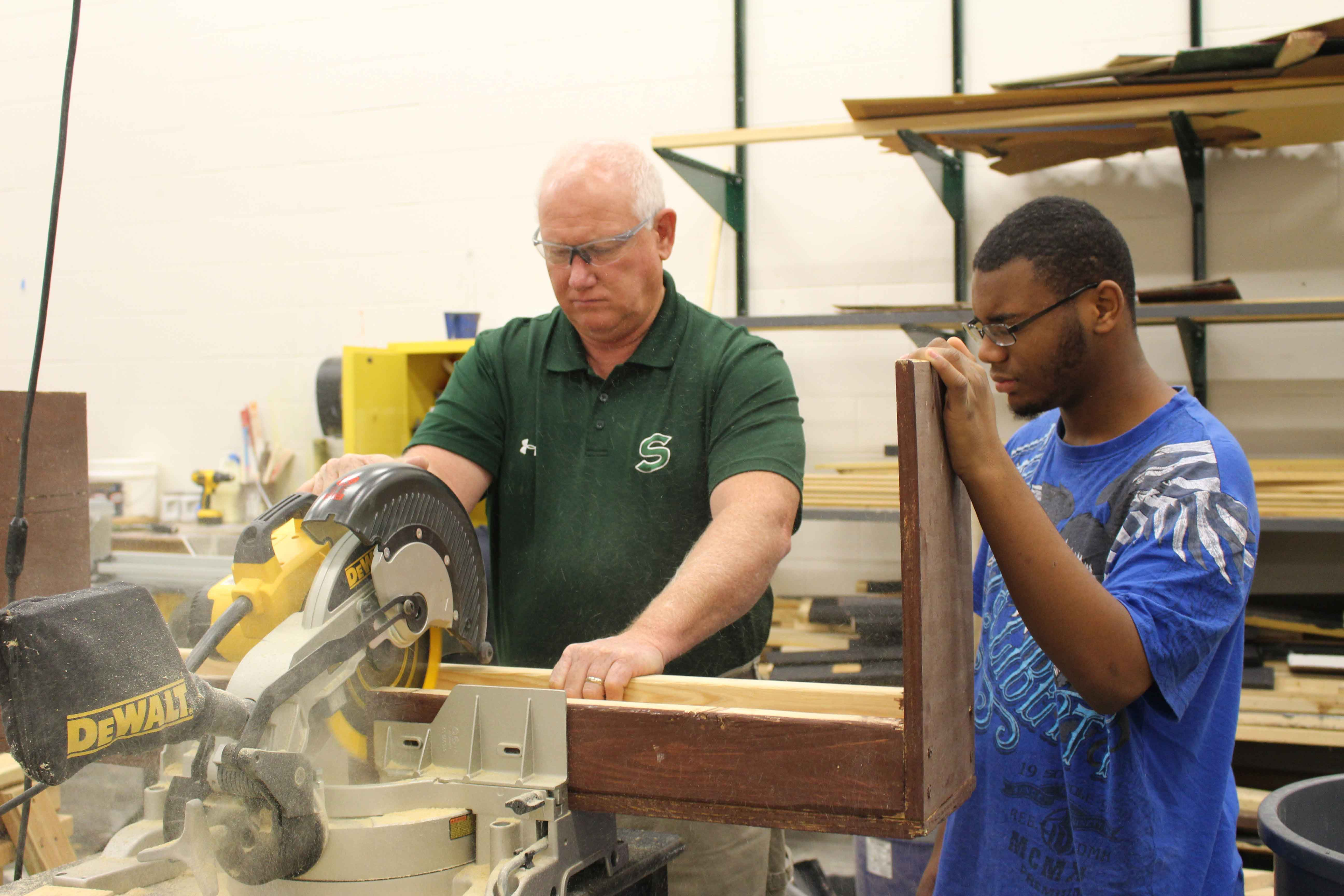 """•Showing sophomore Jerry Burks how to cut a stool, teacher Stephen Dains prepares the props for the musical. The Stagecraft students have been working on the set a month in advanced. """"We're taking some of the old props that they had, and modifying them so that they work for what they're doing this time,"""" said Dains. """"We're also building a few props from scratch."""""""