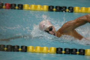 """Taking a breath, junior Noah Reid swims freestyle. He has been swimming since he was nine. """"It gives me a lot of life traits, like haw to manage my time. Hard work definitely pays off,"""" Reed said."""