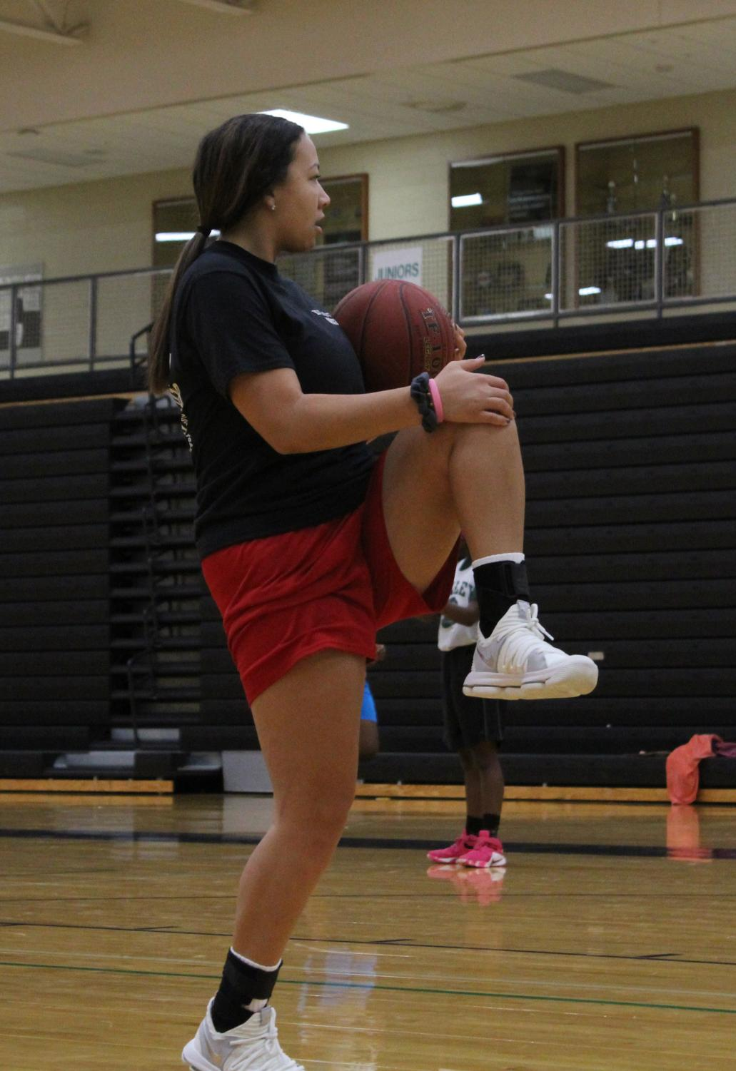 """Warming up for basketball practice Nov. 4, senior Emilyn Richardson is preparing for practice. Joining the team this year, Richardson is eager to get the season started. """"It's going to be a fun and exciting season. Yes, we will have some ups and downs but that's just part of it."""""""