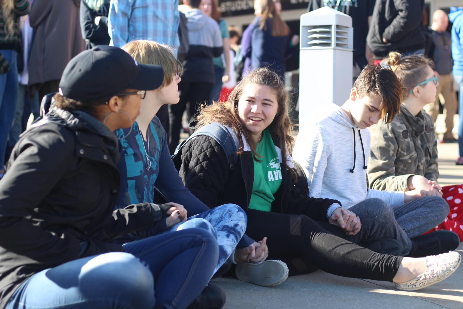 """While participating in the walkout on March 14, sophomores Lexi Valdez, Naomi Davis, Maria Engemann, Tanner Sneed and Shayla Crumb-Potmesil sit and hold hands out of respect for the 17 victims of the Parkland, Fla., school shooting. #NationalWalkoutDay was trending globally on Twitter to cover all the walkouts  across the country. """"We wanted to sit down to make it better because everyone else was standing and talking and laughing, instead of paying attention to the ones who passed away,"""